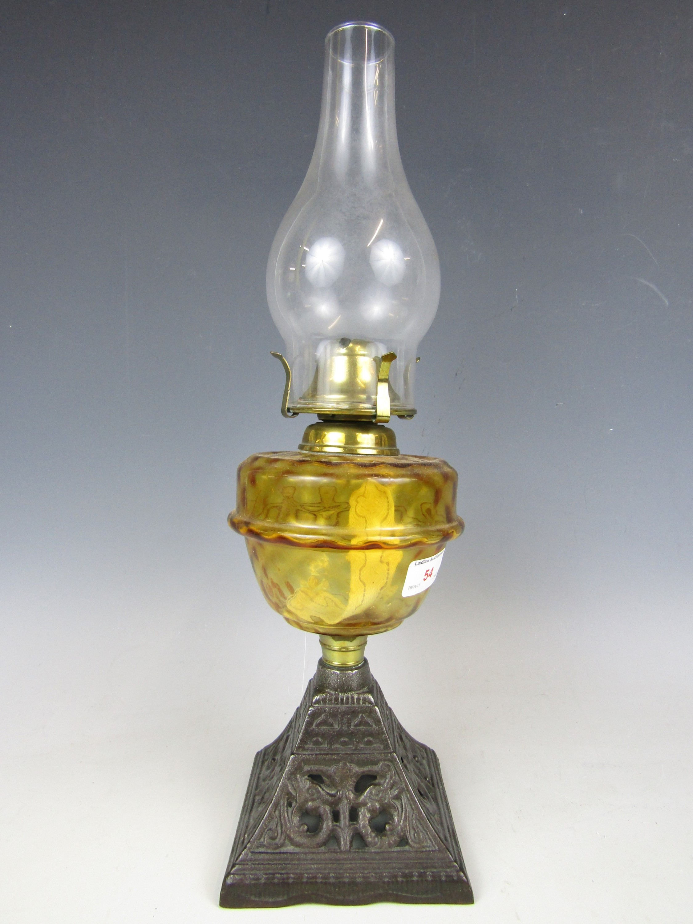 Lot 54 - A 19th Century oil lamp with amber glass reservoir and cast base