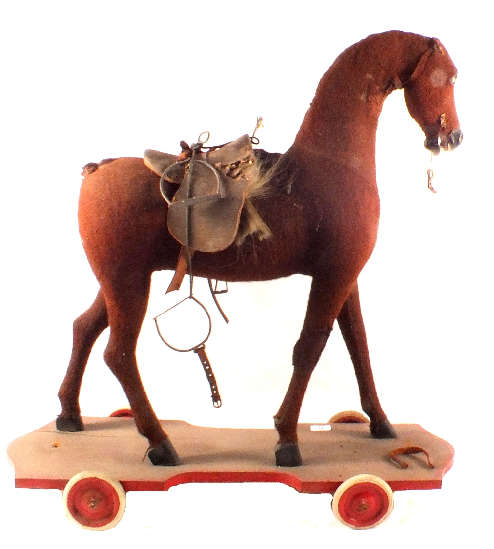 Lot 41 - A wooden wheeled horse with felt hide and leather saddle,