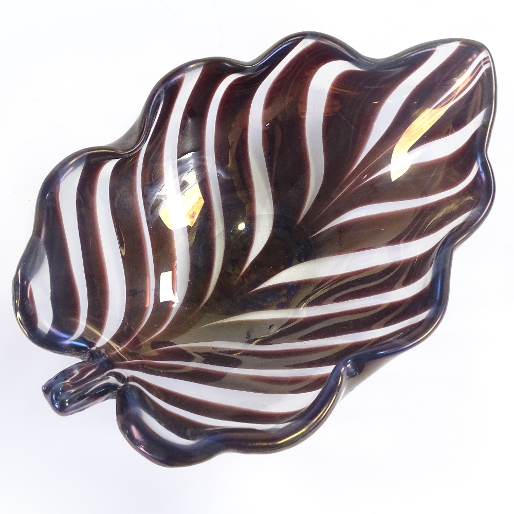TYRA LUNDGREN FOR VENINI - a 1930s thick Murano glass leaf bowl, amethyst coloured stripes with wave