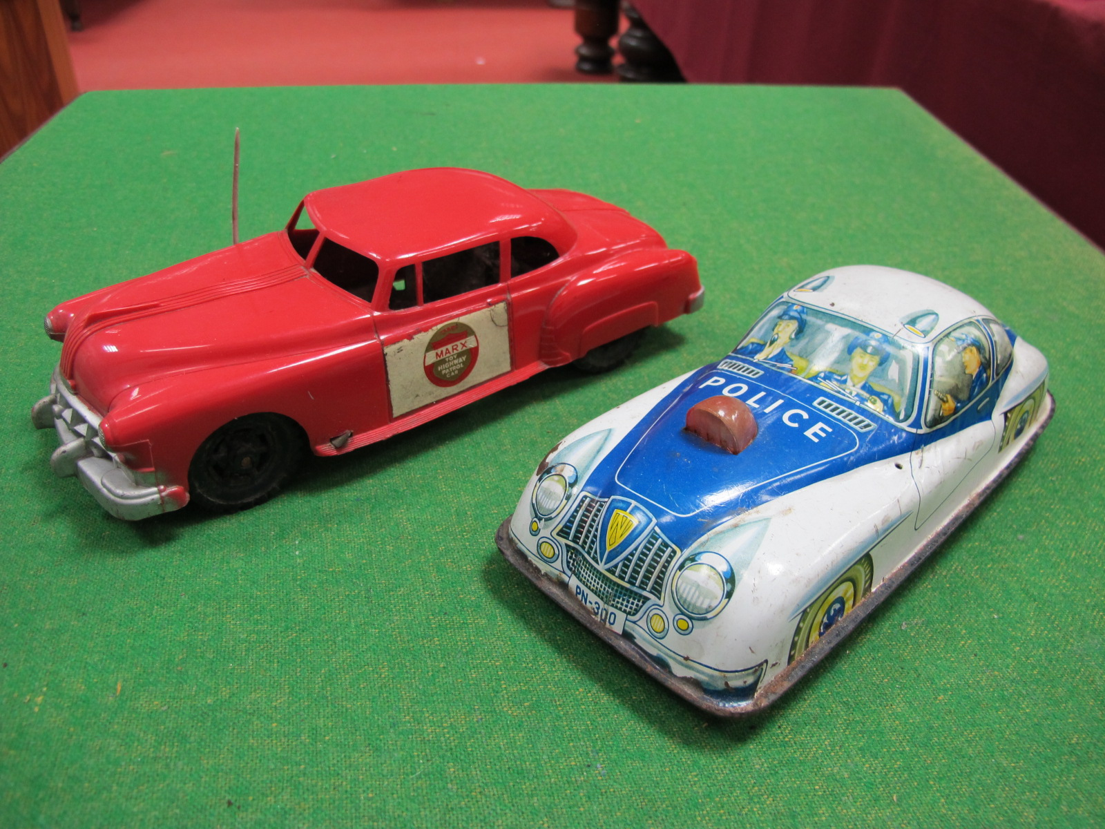 Lot 543 - A 1950's Plastic Police Car, by Marx, friction drive, red plastic, 24cm long, plus a tinplate police