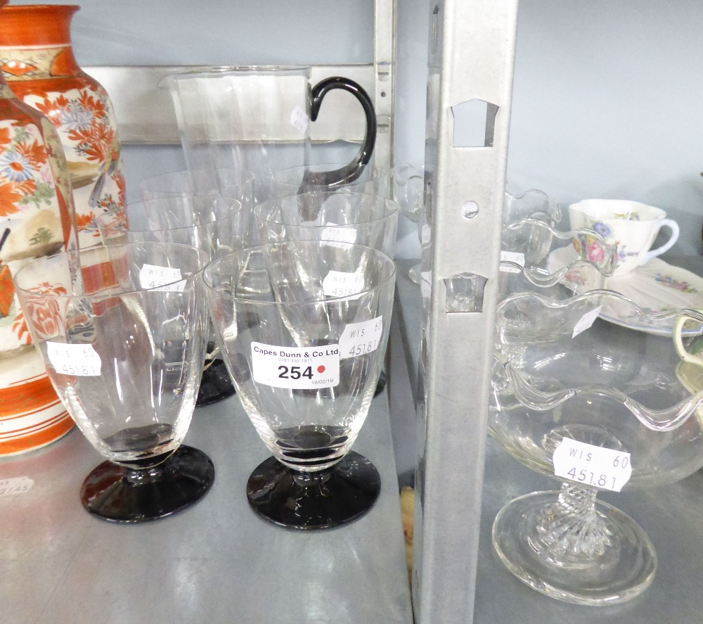 Lot 254 - A GLASS WATER JUG WITH BLACK GLASS HANDLE AND BASE; A SET OF SIX MATCHING GOBLETS; A SET OF FOUR