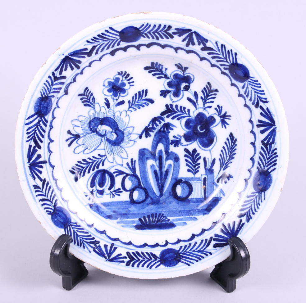 "Lot 1 - A 19th century English delft dish, decorated with flowers and fence, 9"" dia"