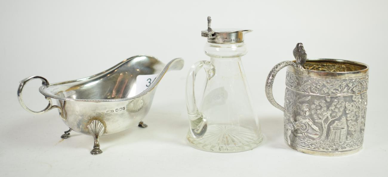 A Georgian style silver sauceboat, Sheffield, 1932; a silver topped glass whisky noggin, Birmingham,