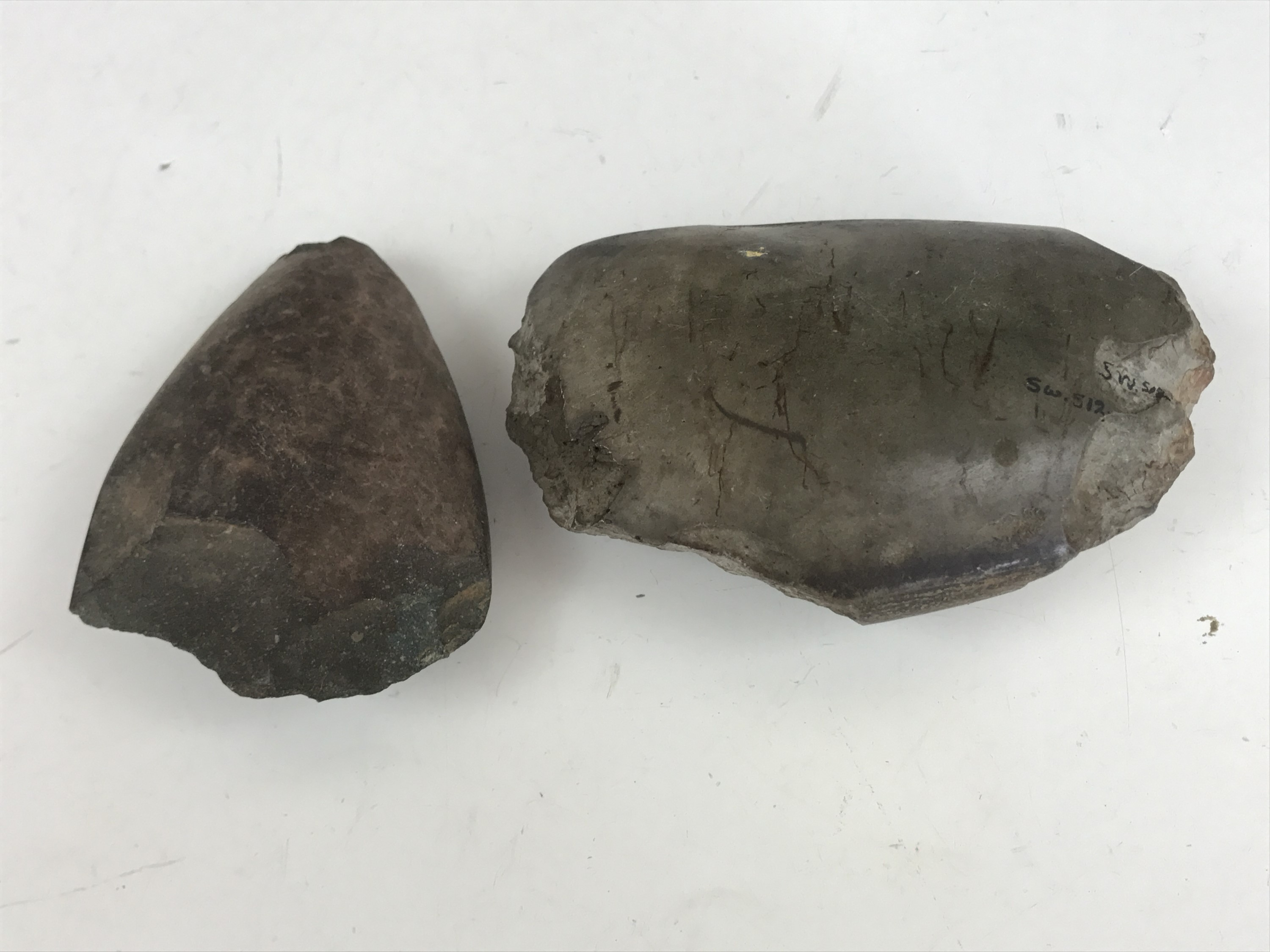 Lot 9 - Two Neolithic / Bronze Age polished stone hand axes, one bearing old collection inventory number