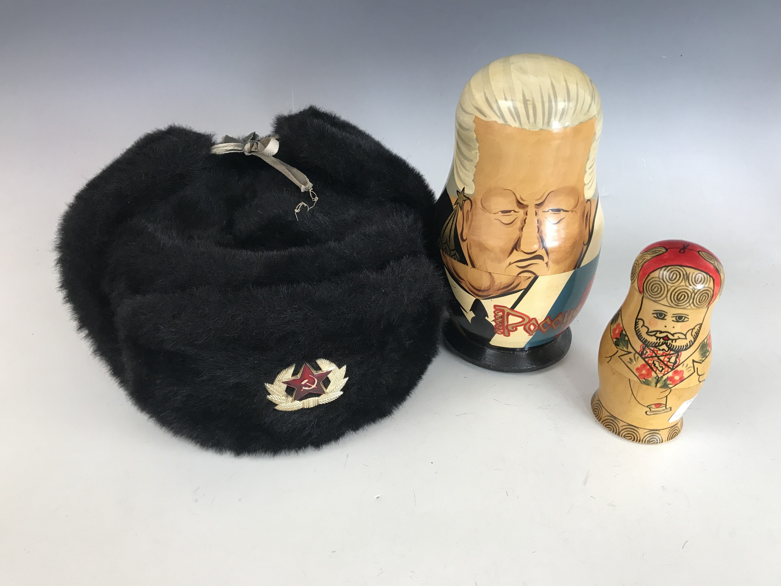 Lot 54 - A Glasnost period caricature Russian Marushka doll together with one other and a Soviet fur hat