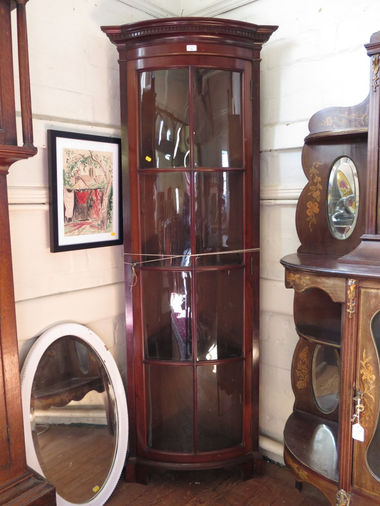 Lot 53 - A 1930s mahogany corner cabinet, the dentil cavetto moulded cornice over a long glazed door on