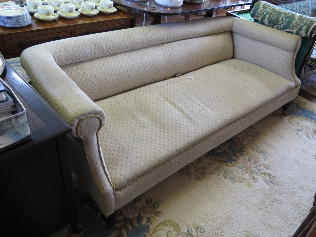 Lot 33 - An Edwardian upholstered settee, the fully upholstered scroll back and arms on turned legs and brass