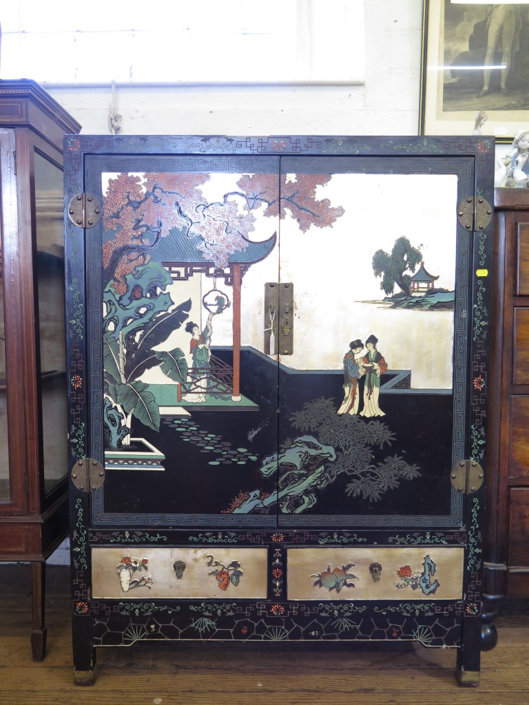 Lot 27 - A painted and lacquered Oriental cabinet, depicting figures and birds in garden scenes, the pair