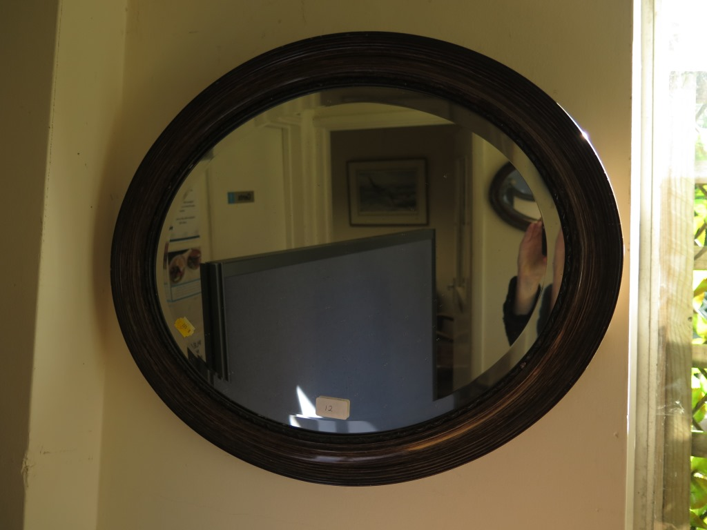 Lot 12 - An oval oak framed mirror 67cm wide and another oval mirror 59cm wide
