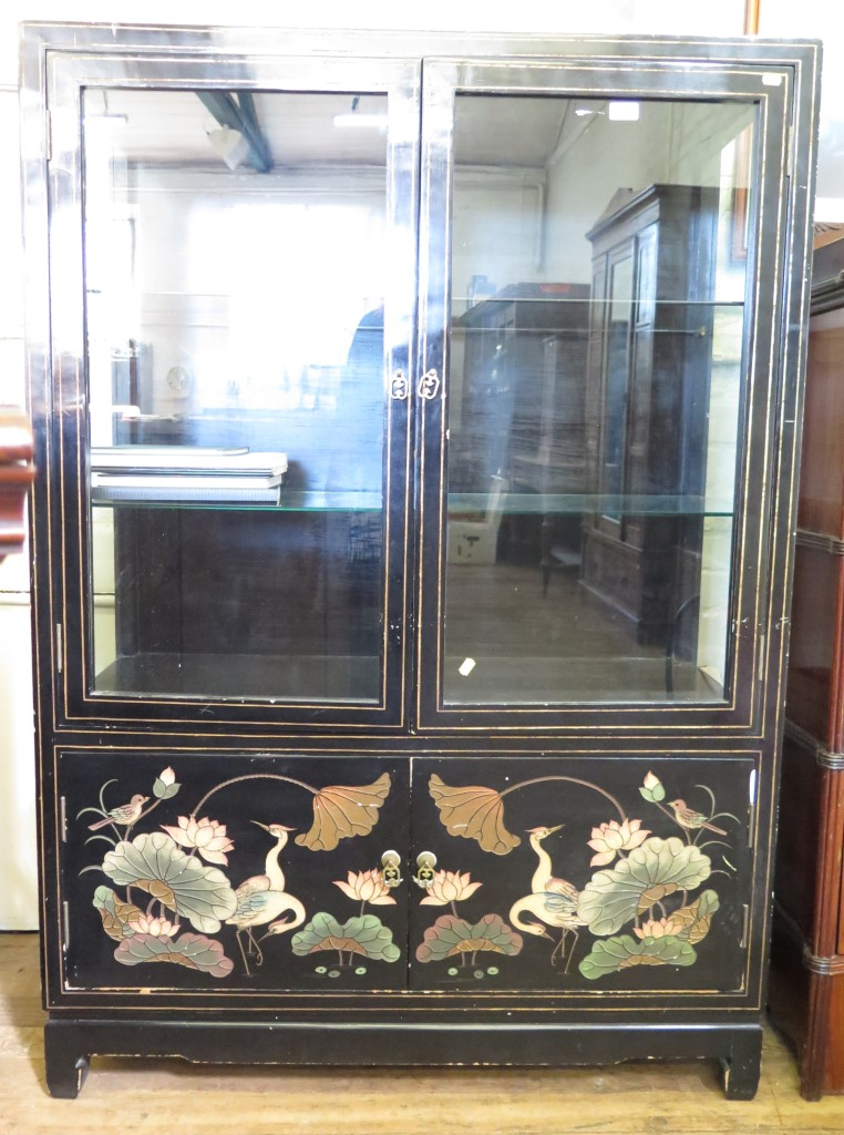 Lot 7 - An Oriental black lacquered display cabinet, the twin glazed doors over a pair of doors depicting