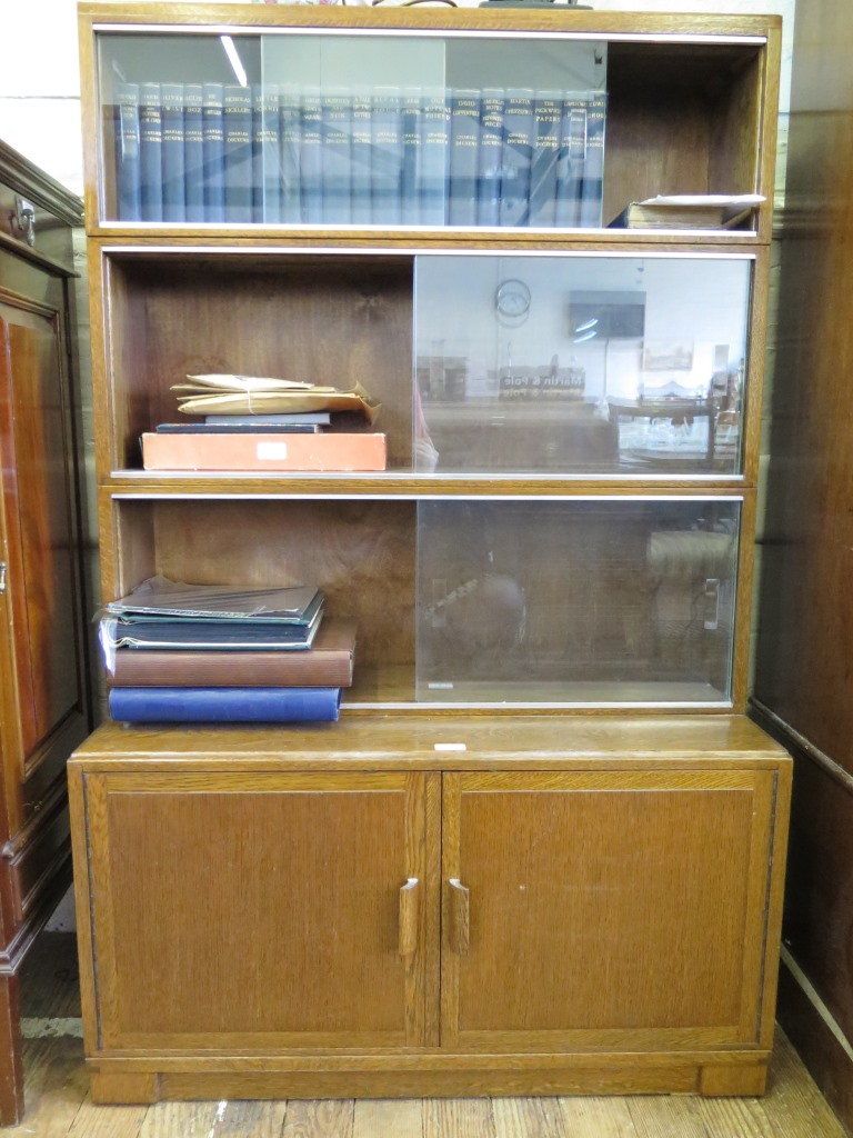Lot 9 - An oak Minty stacking bookcase, with three tiers of shelves with sliding glass doors above a pair of