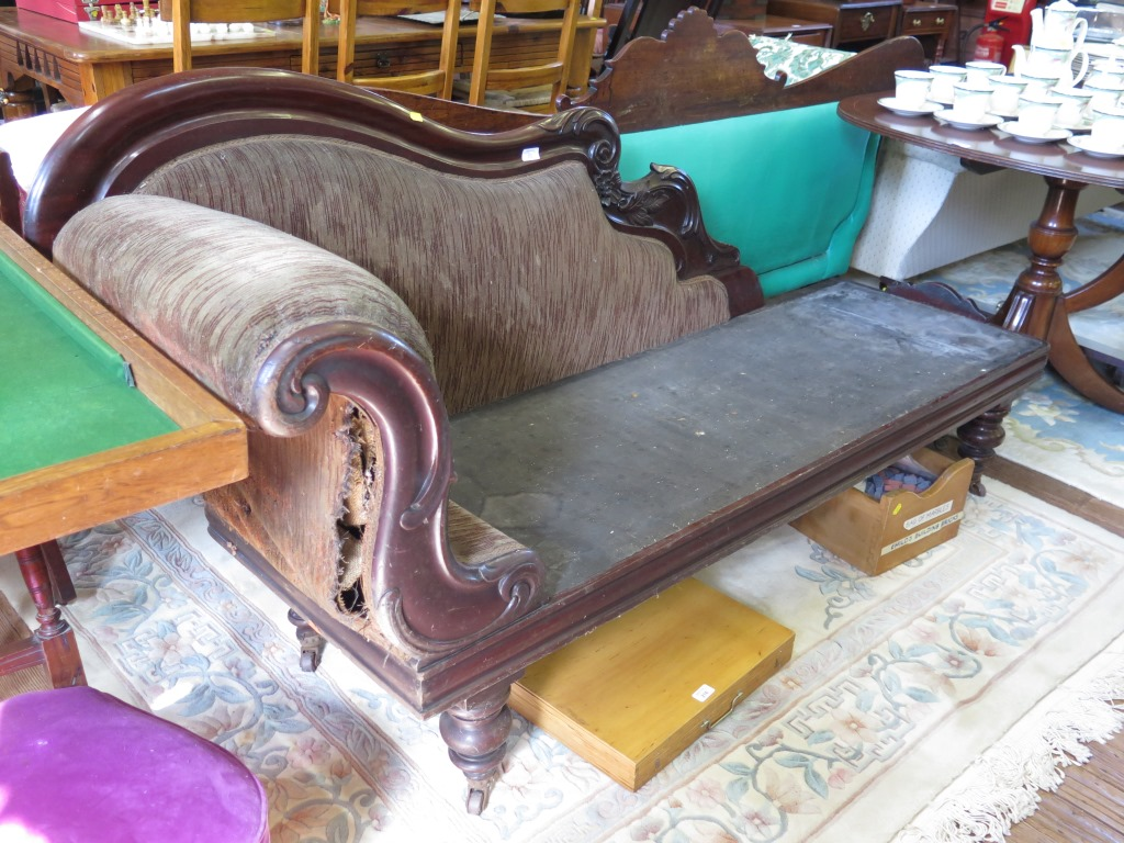 Lot 23 - A mid Victorian mahogany chaise lounge, with carved three quarter back, and scroll arm on turned