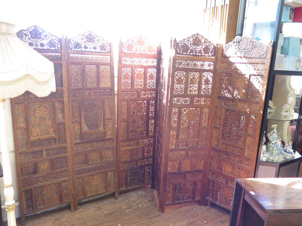 Lot 34 - An Indian carved hardwood six fold screen, profusely carved with scrolling leaf motif, each panel,