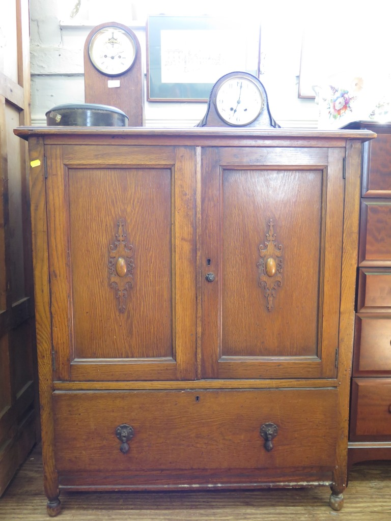 Lot 1 - A 1930s oak cabinet, the twin panelled and cabochon applied doors over a long drawer on turned feet,