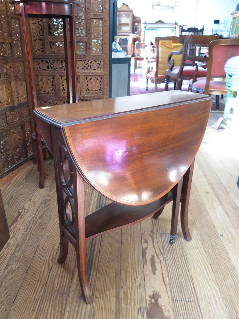 Lot 29 - A mahogany and satinwood crossbanded Sutherland table, the oval top over fret carved supports on