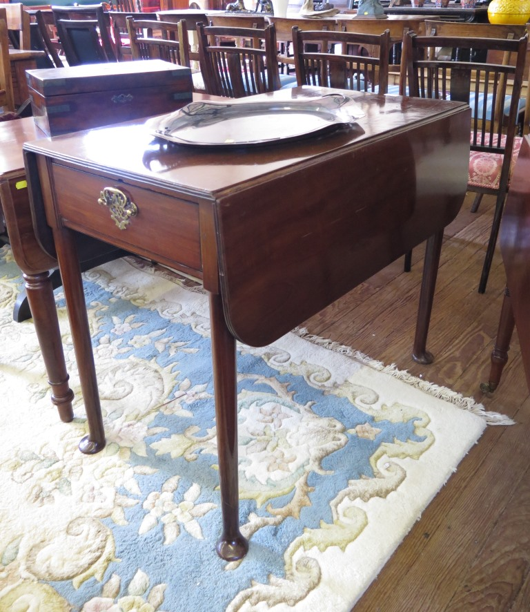 Lot 56 - A George III style mahogany Pembroke table, the rounded leaves over a frieze drawer on turned legs