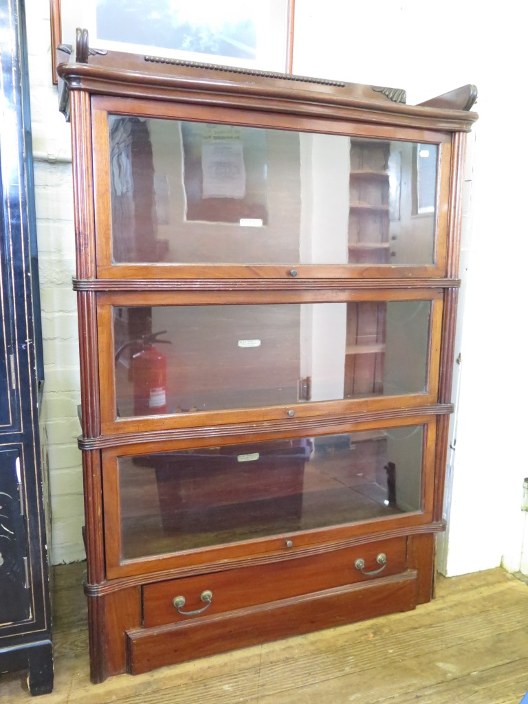 Lot 8 - A Globe Wernicke mahogany stacking bookcase, the raised back over three glazed serpentine tiers over