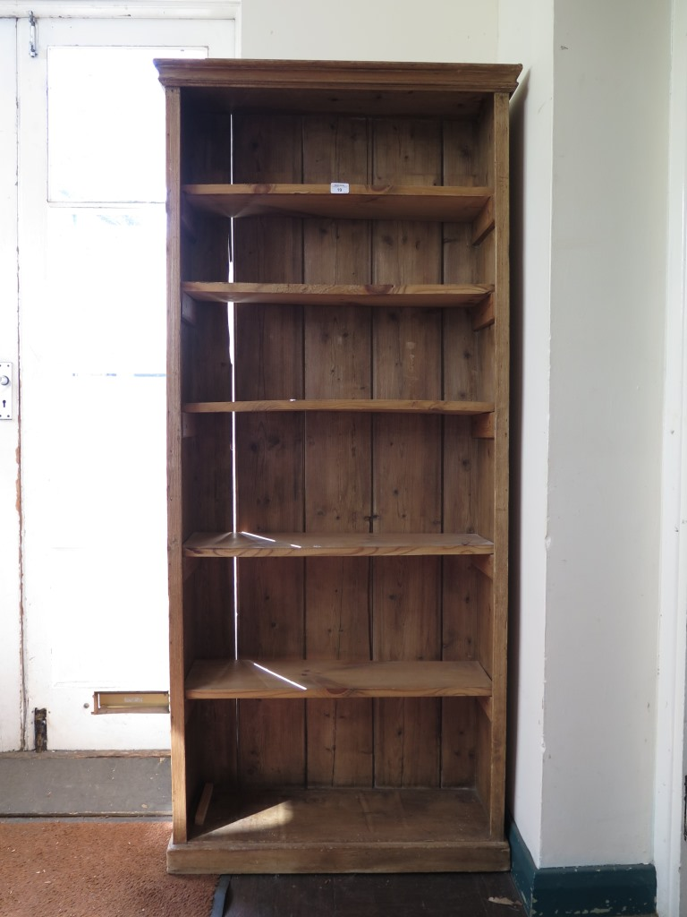 Lot 19 - A pine open bookcase, with moulded cornice and plinth base, 75cm wide 169cm high