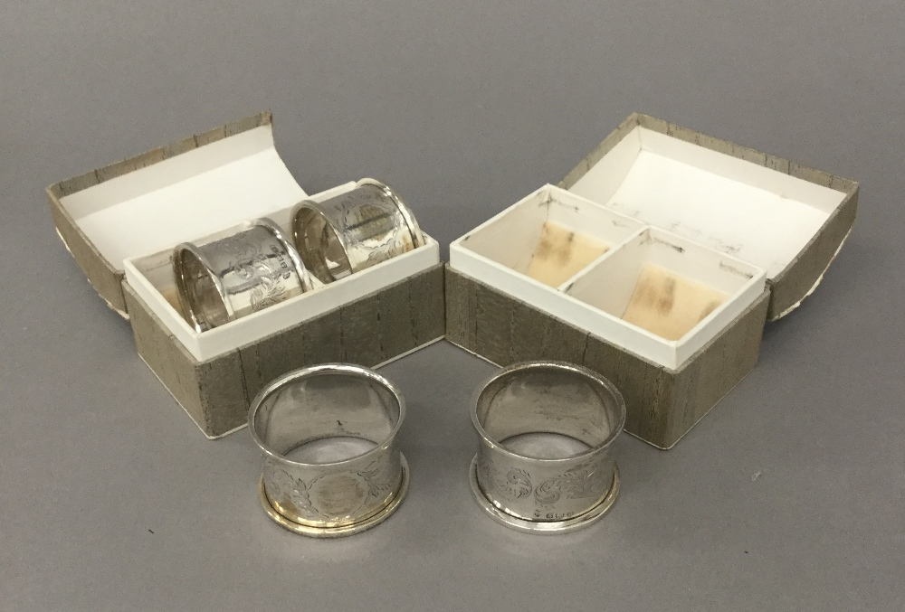 Four boxed silver napkin rings (59 grammes)