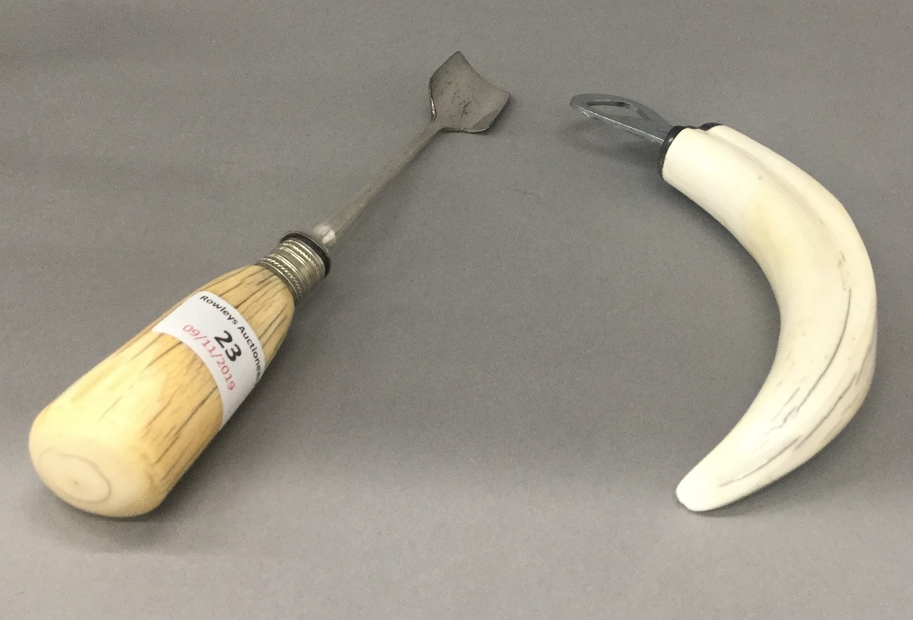 A 19th century ivory handled cheese scoop and a boar tusk bottle opener