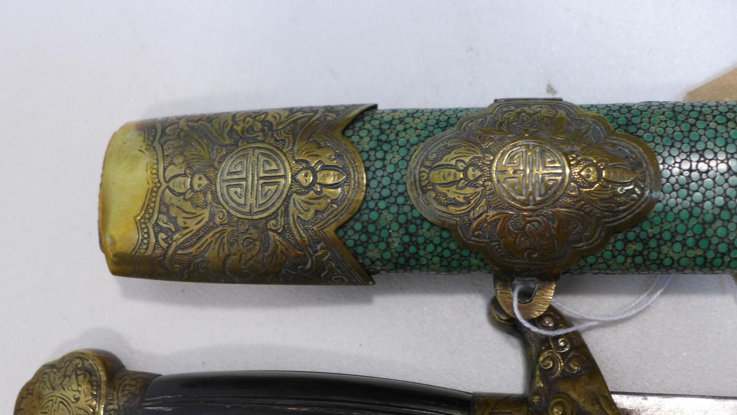 Lot 1 - A Chinese late Qing dynasty double sword, with cast brass mounts and horn grip, in shagreen