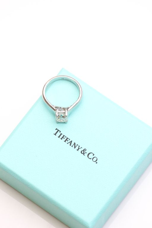 Lot 10 - A Tiffany and Co diamond solitaire platinum ring, the emerald cut diamond accompanied by a Tiffany