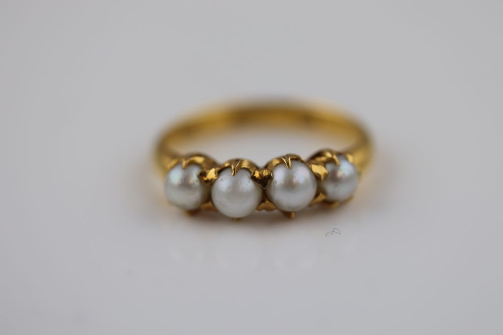 Lot 26 - A four stone pearl unmarked gold ring, probably 18ct, claw set pearls, ring size O½