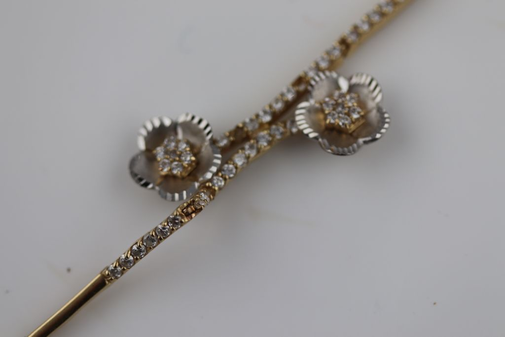 Lot 22 - A white stone 14ct yellow and white gold bracelet, floral design, tongue and box snap clasp,