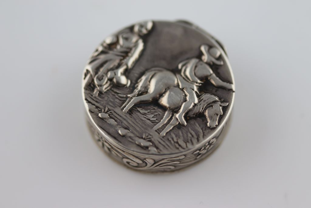 Lot 56 - An Edwardian silver circular patch box, repousse rustic country scene to lid of rider on horse