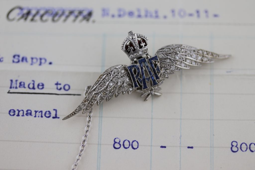 Lot 51 - A diamond, sapphire and enamel white gold Royal Air Force (RAF) 'Wings' sweetheart brooch, seventy