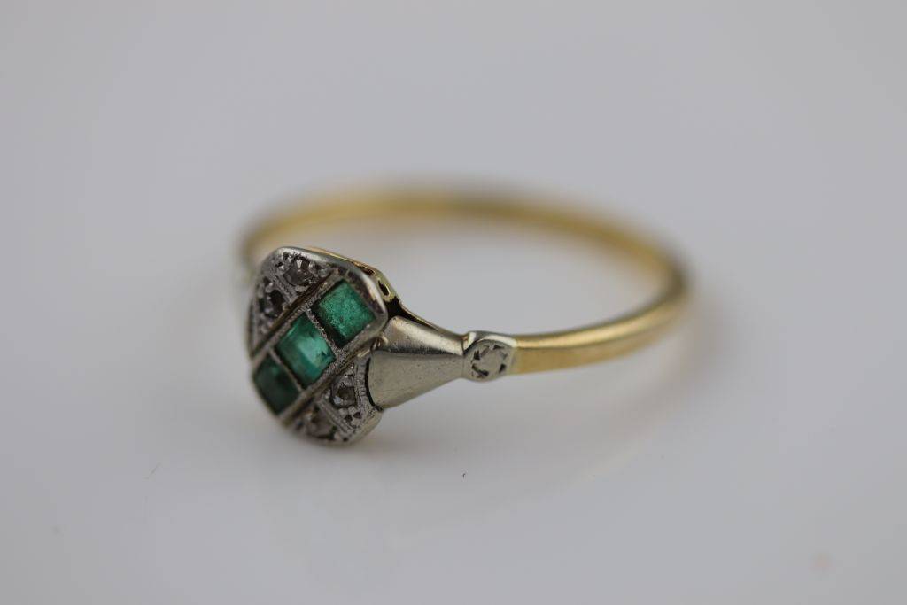 Lot 7 - An Art Deco emerald and diamond 18ct yellow gold platinum set ring, the rounded rectangular head