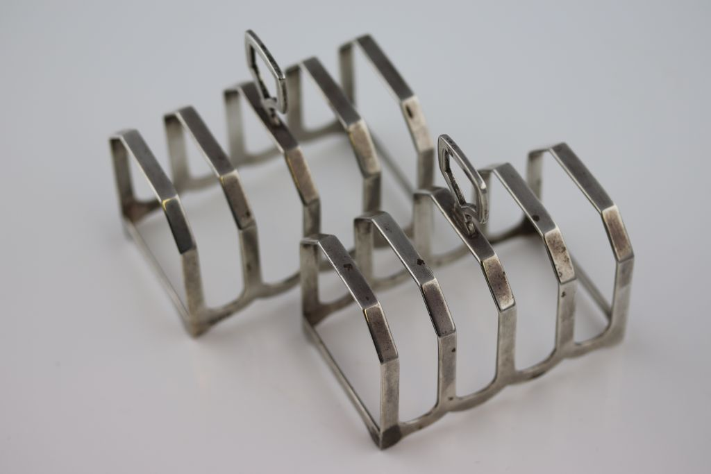 Lot 11 - A pair of silver five bar toast racks, trapezoid form with fluted base, height approximately 8cm,