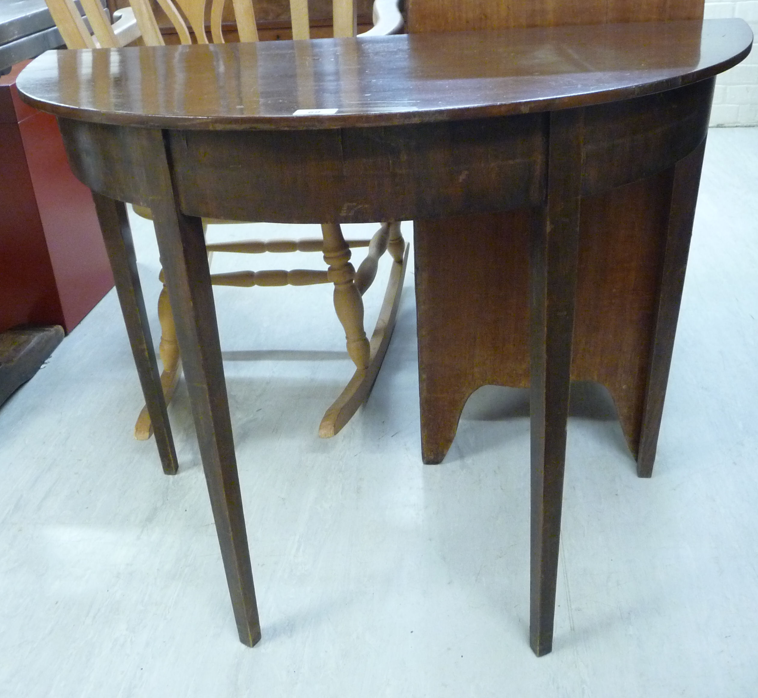 Lot 69 - An early 20thC mahogany demi-lune console table with a straight apron, raised on square,