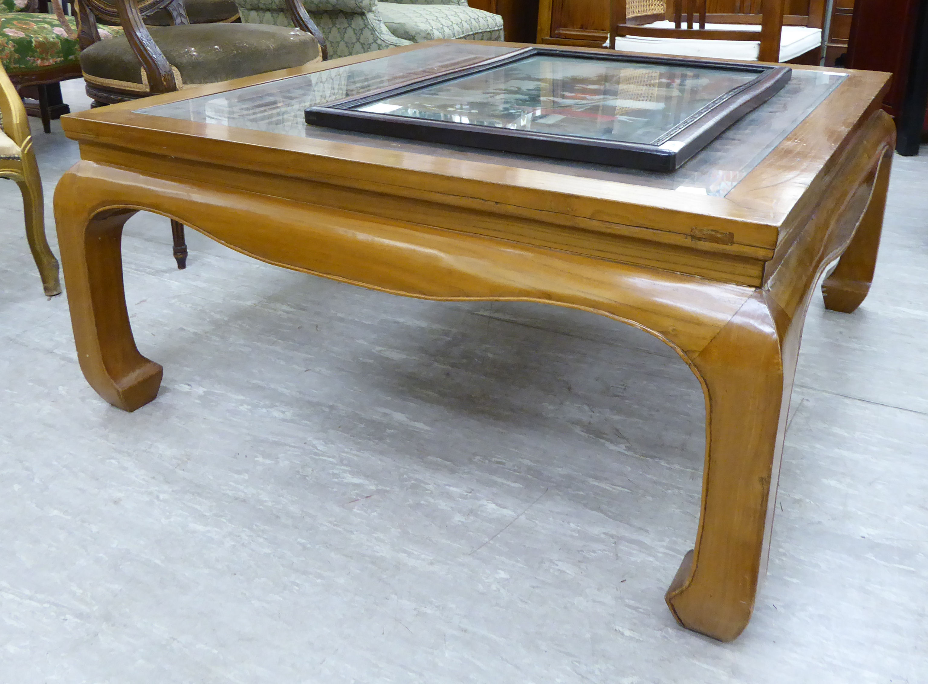Lot 36 - A modern Chinese lacquered elm coffee table, the openwork top with a glass panel, raised on carved,