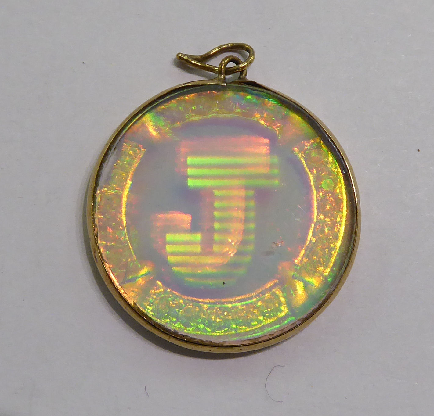 Lot 81 - A gold coloured metal hologram pendant with the initial 'J' 11