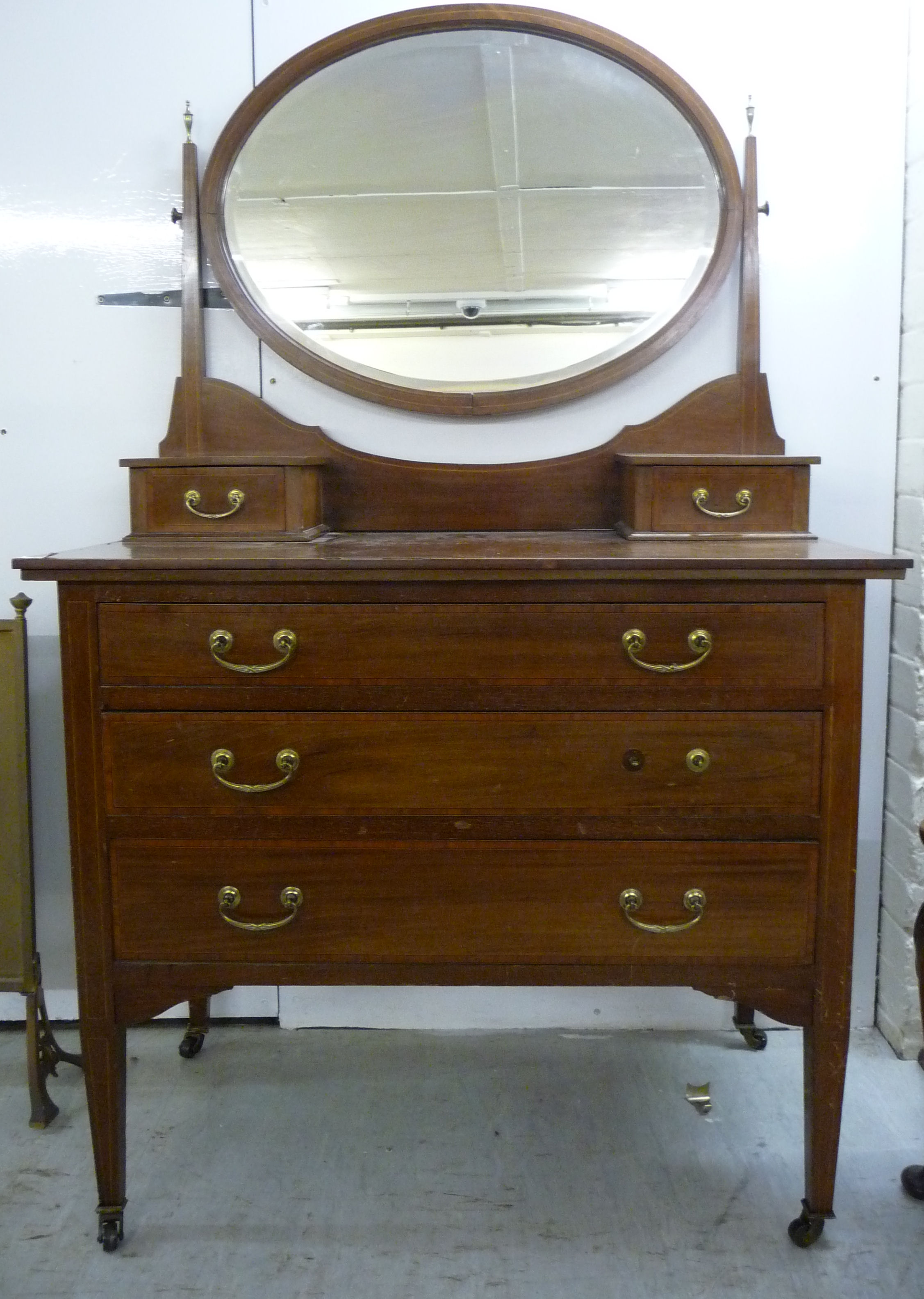Lot 53 - An Edwardian satinwood string inlaid mahogany dressing table, surmounted by an oval interior,