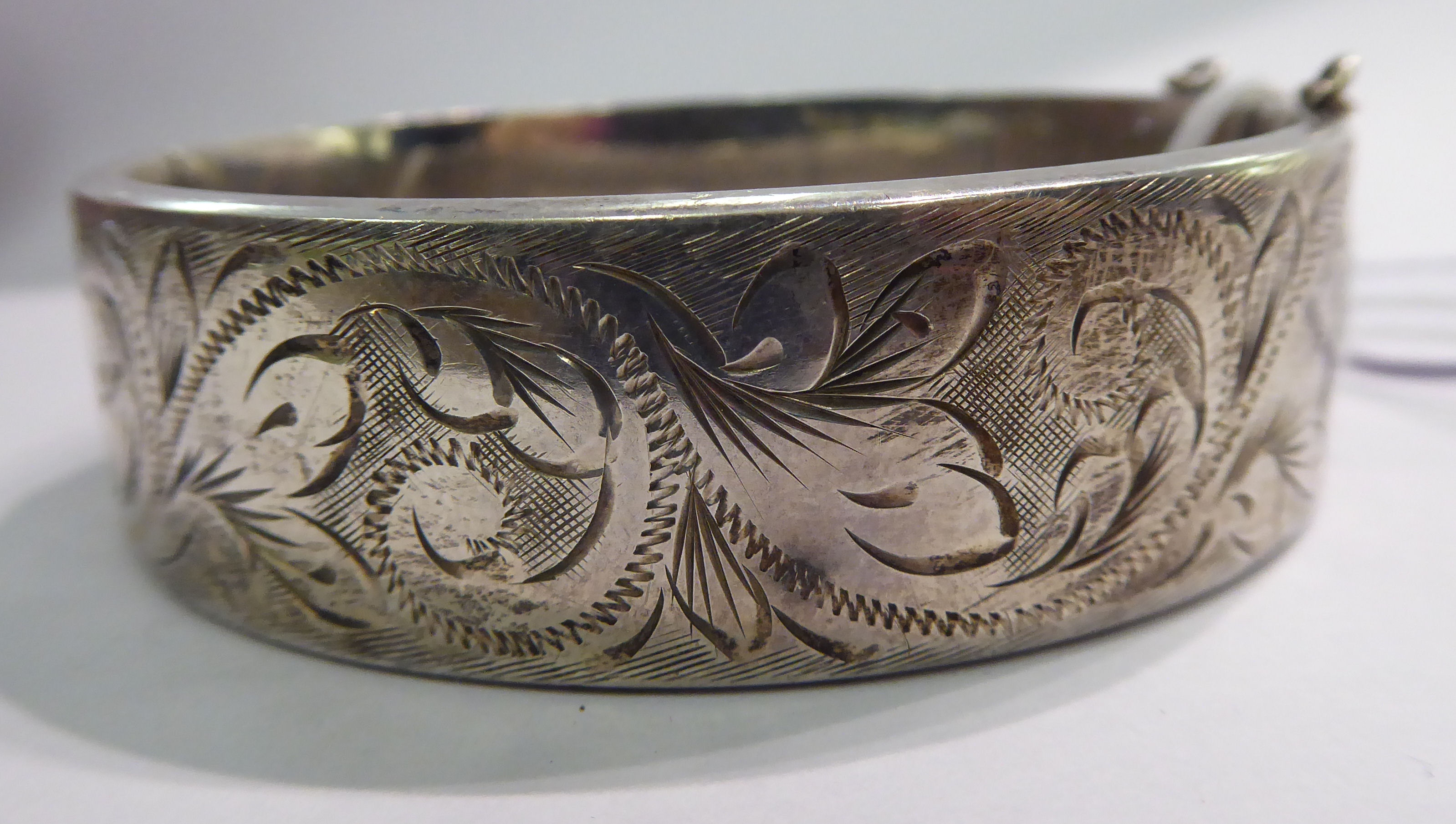 Lot 61 - A silver hollow bangle with engraved foliate ornament Birmingham 1974 11