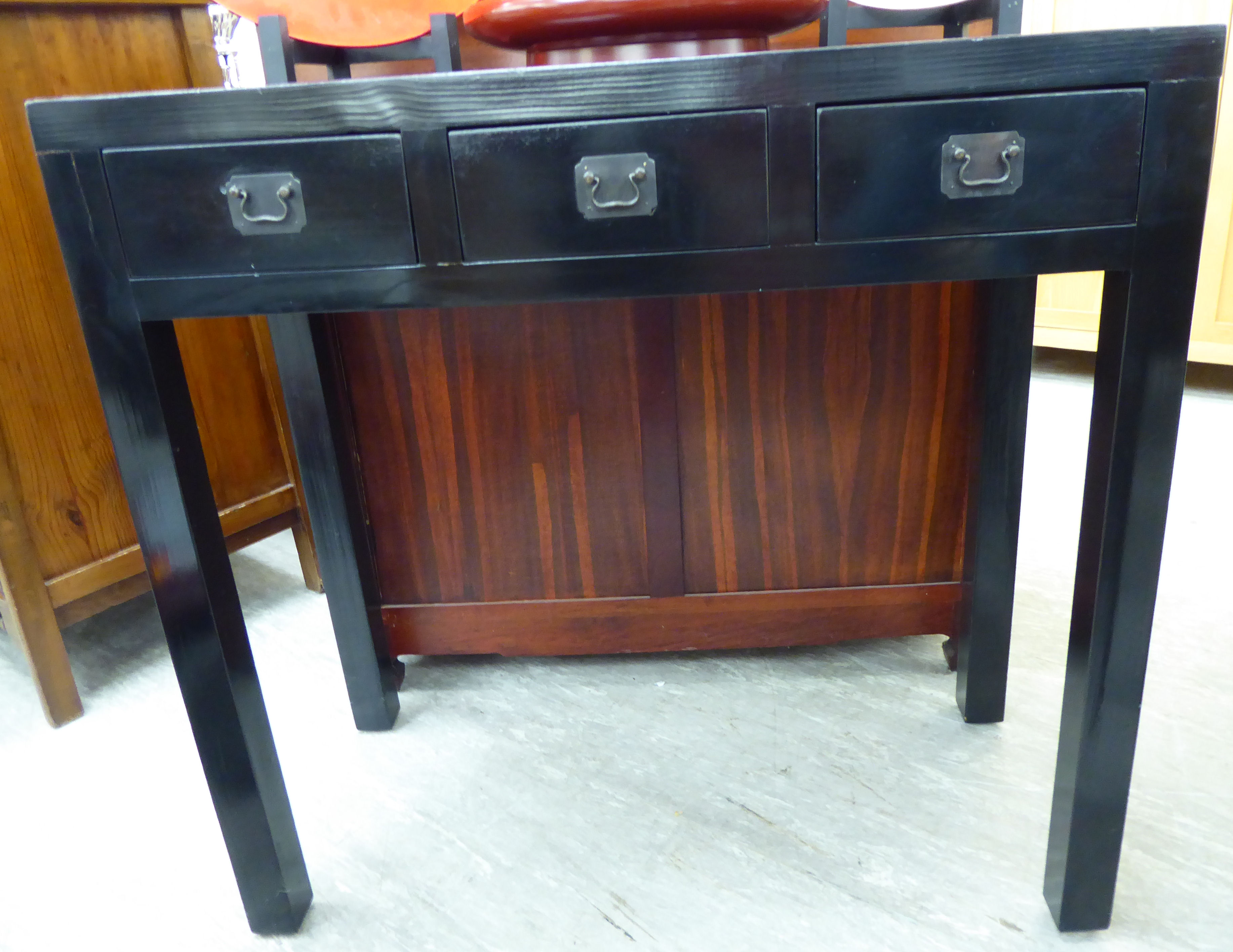 Lot 45 - A modern Chinese black lacquered hall table, the top with a mitred edge with three frieze drawers,