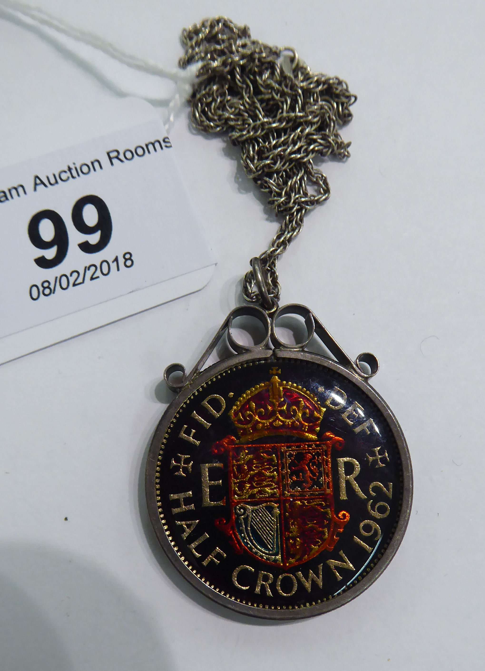 Lot 99 - A 1962 enamelled half-crown, in a white metal mount,