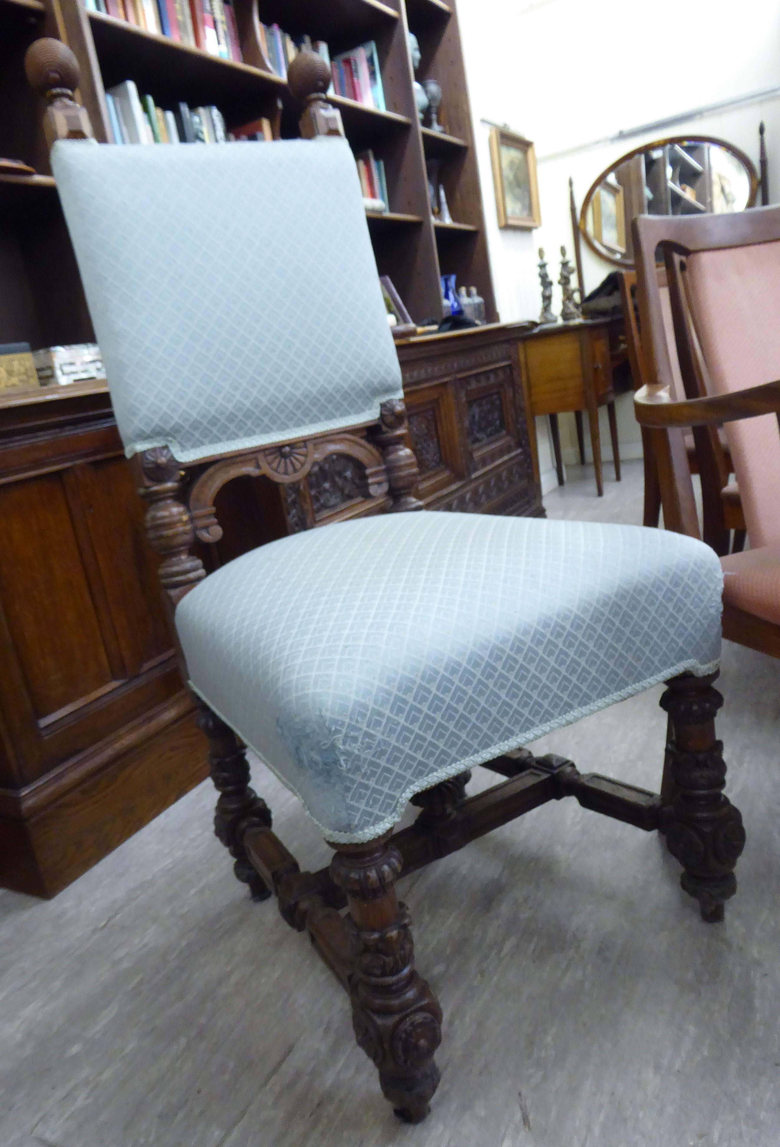Lot 82 - An early 20thC Colonial carved oak showwood framed hall chair,