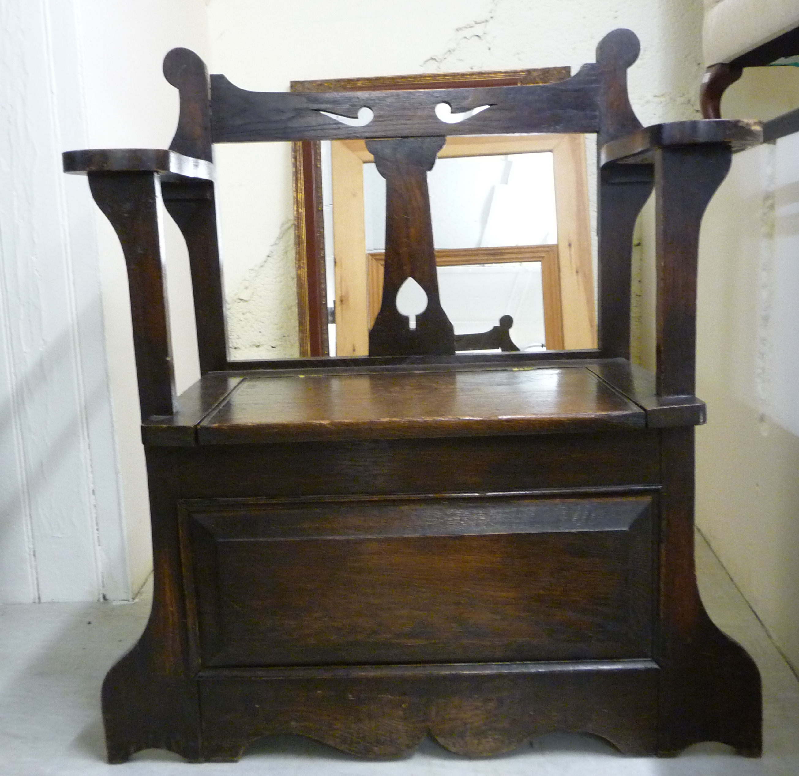 Lot 54 - A 1920s stained oak combination hall seat/stickstand with a low, open back and arms,