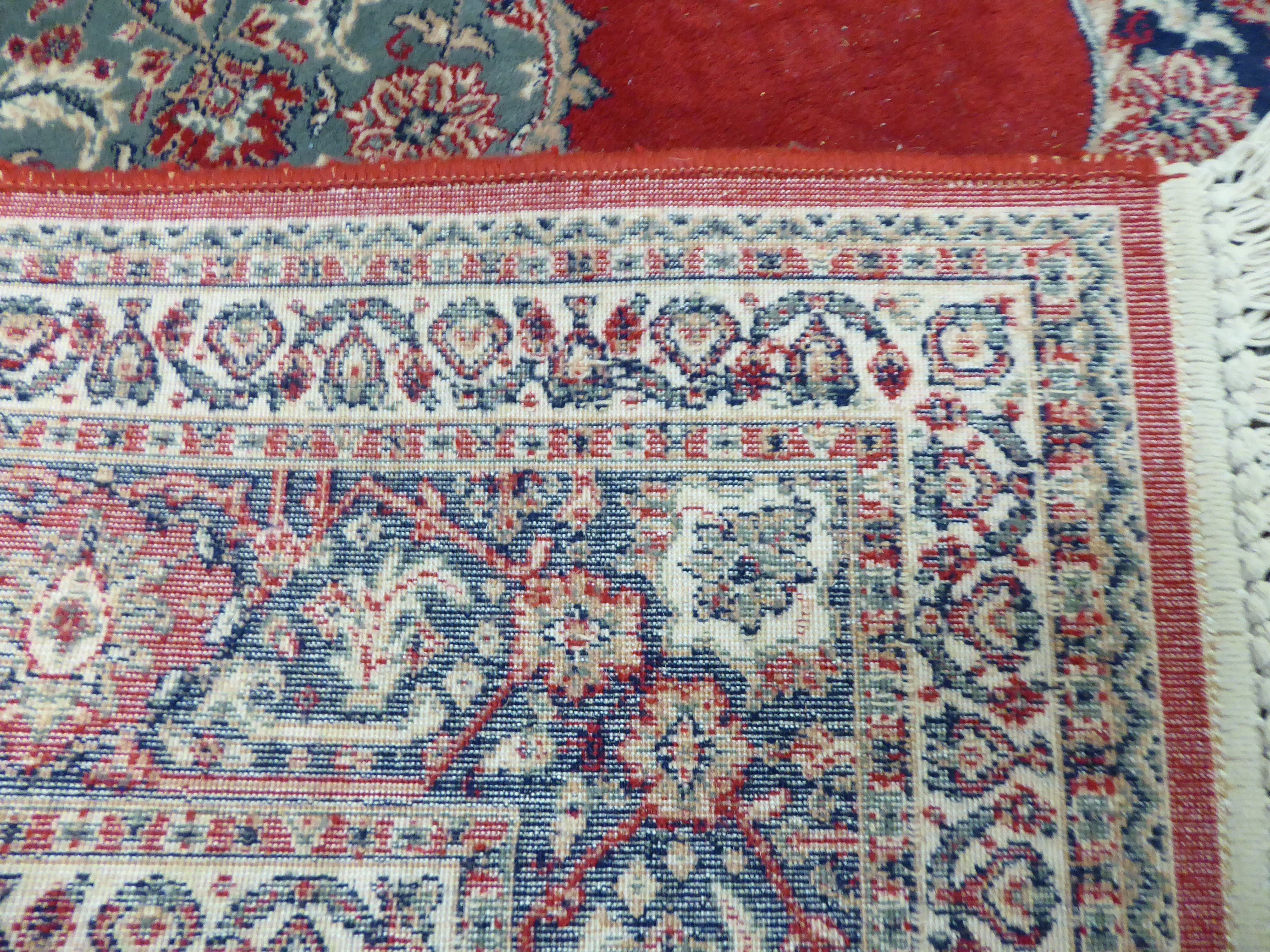 Lot 79 - A Persian rug with a central serpentine outlined motif bordered by stylised flora on a red ground