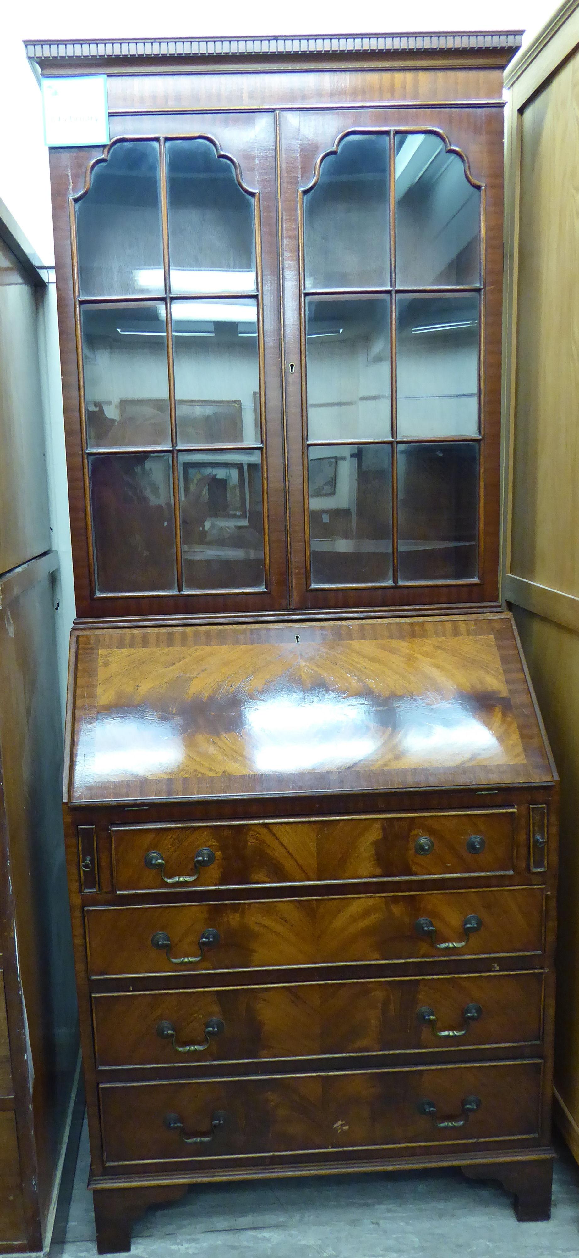 Lot 40 - A modern Georgian style mahogany bureau bookcase with a dentil moulded cornice,