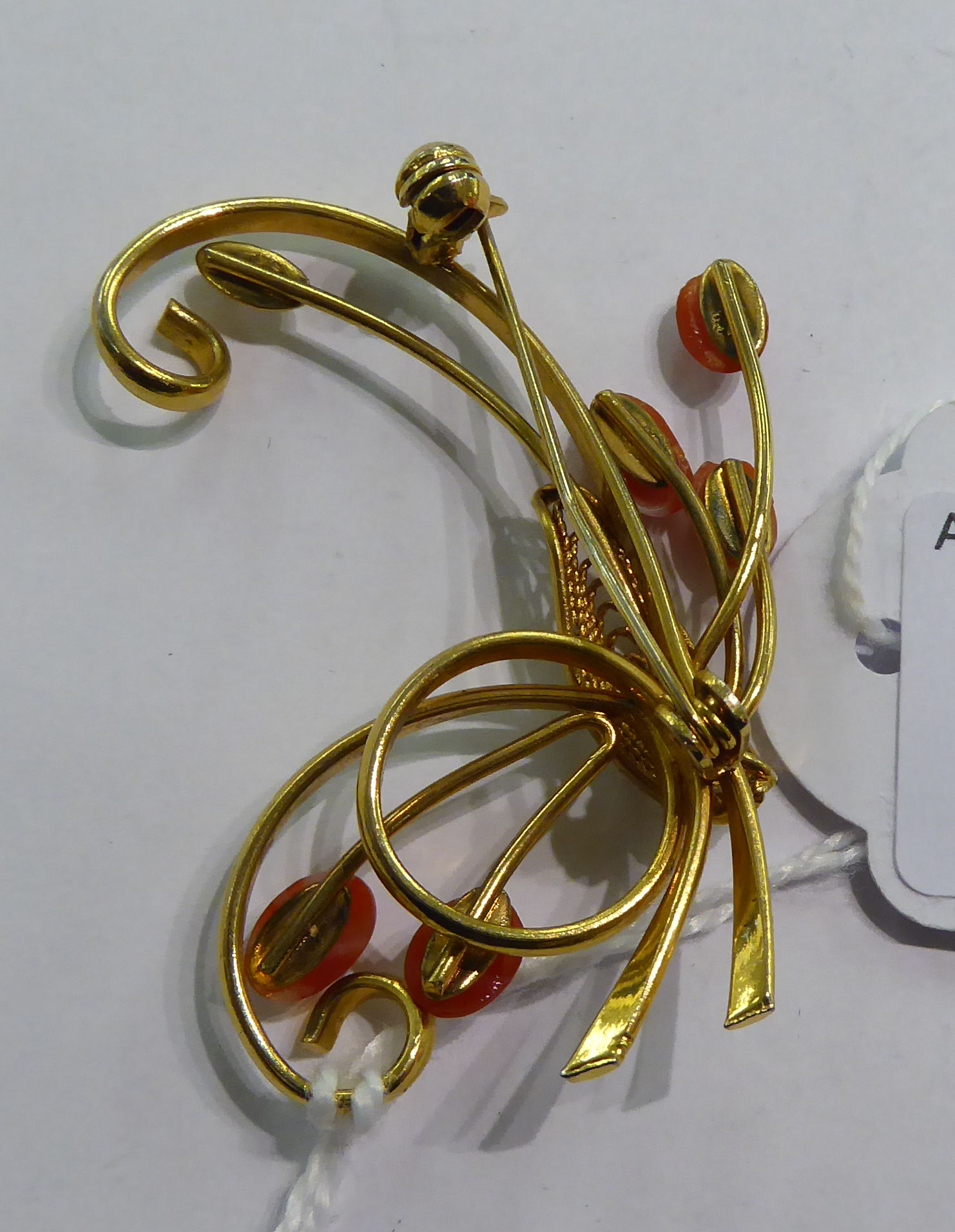 Lot 12 - A gold coloured metal scrolled wire brooch,