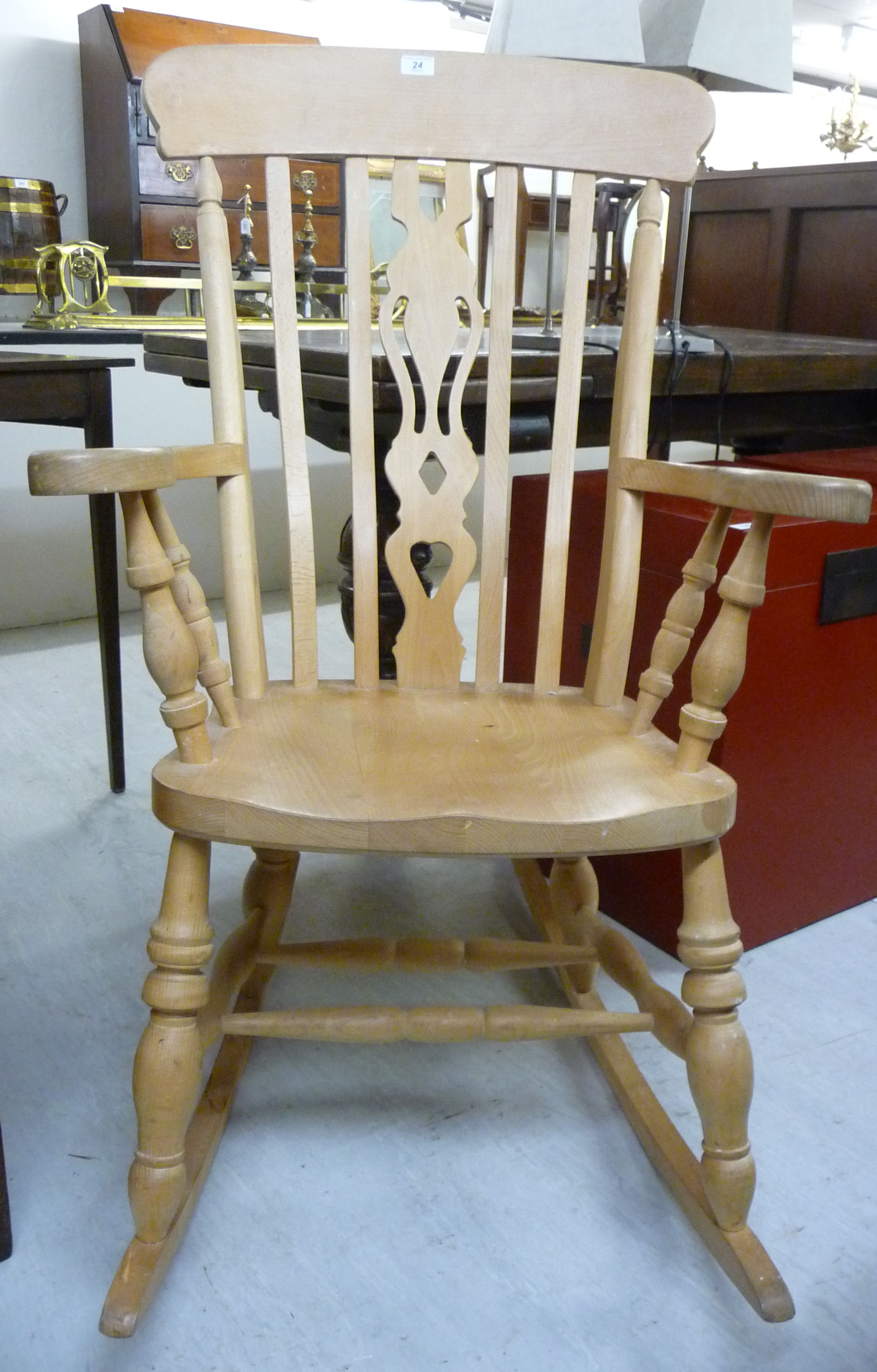 Lot 24 - A modern bleached beech framed Windsor rocking grandfather chair with a high lath back,