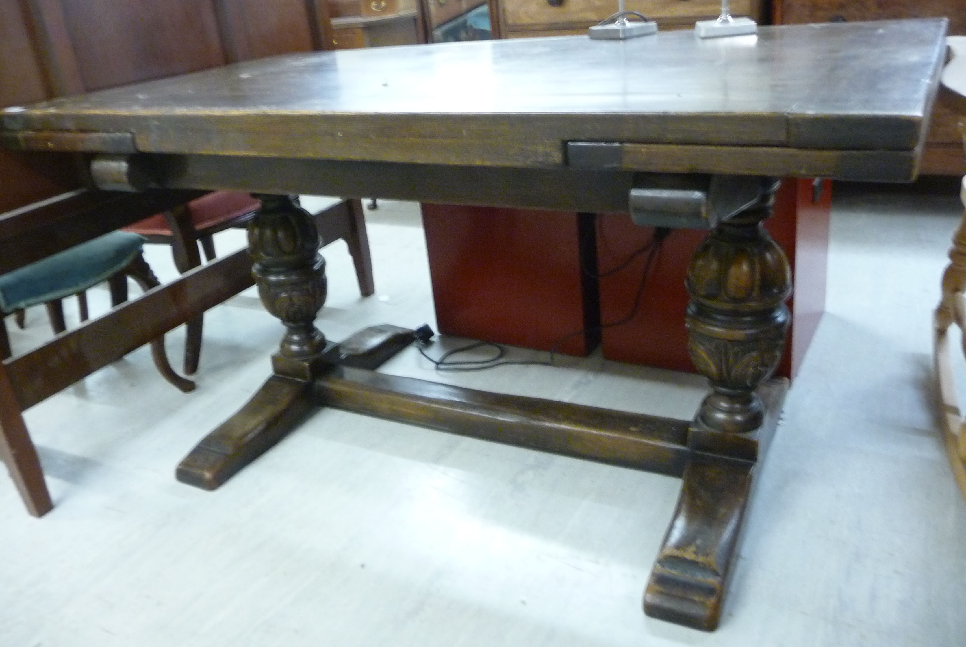 Lot 72 - A 1930s Old English style stained oak, draw leaf refectory table, raised on substantial, twin,