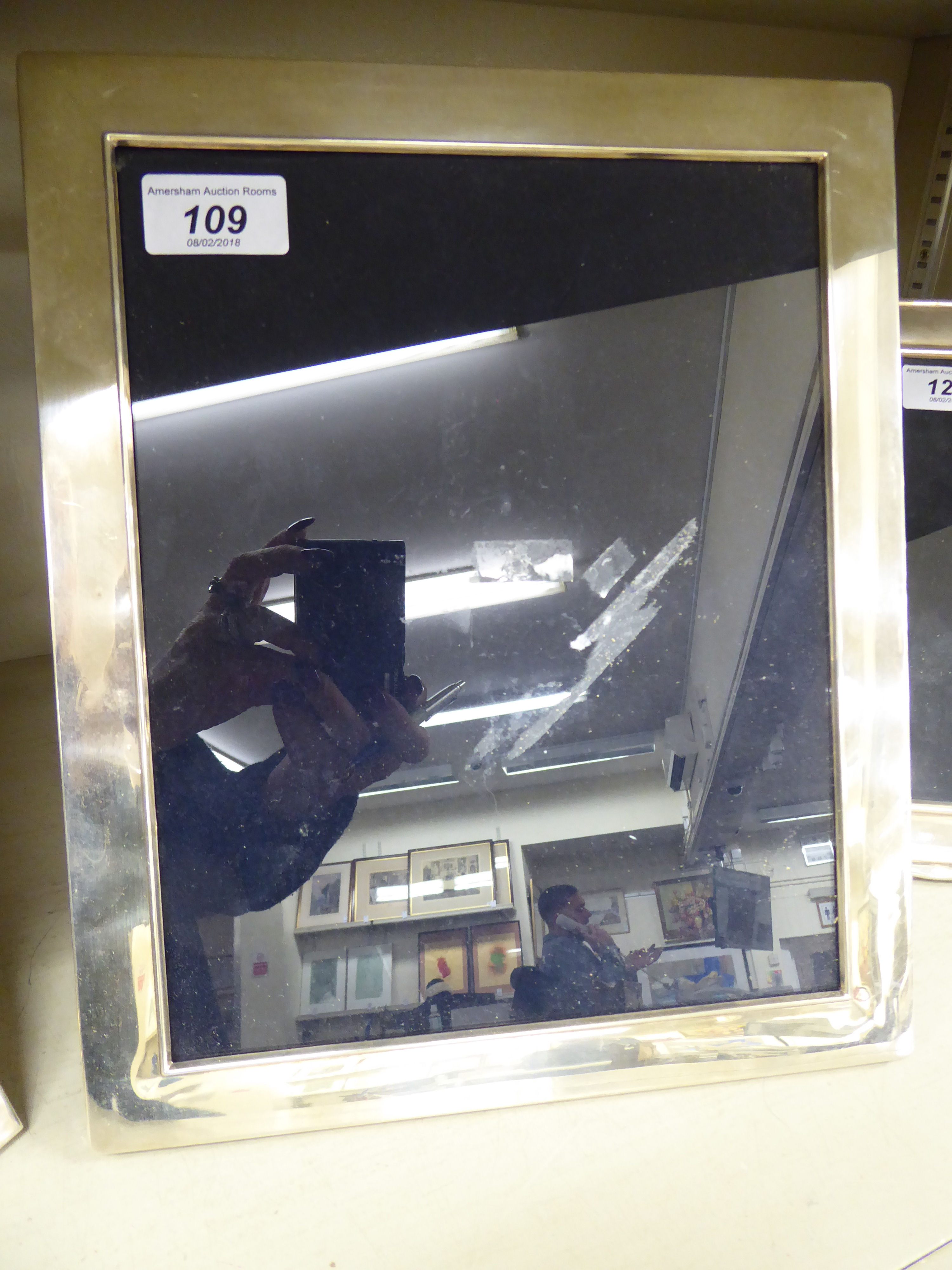 Lot 109 - A glazed silver photograph frame, on a mahogany back and an easel stand London 1977 11.75'' x 9.