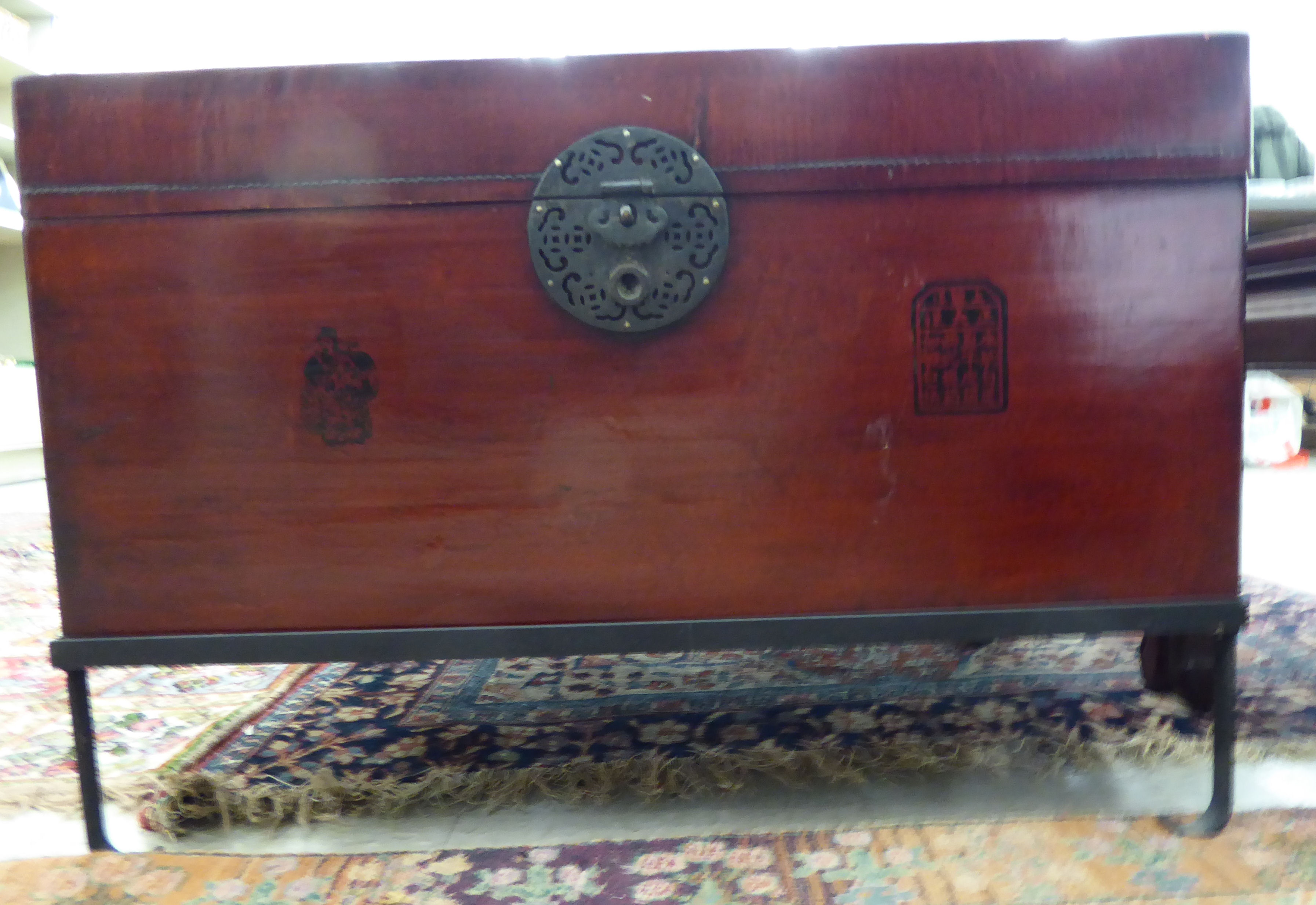 Lot 115 - A modern Chinese lacquered fruitwood chest with a hinged lid and a pierced cast metal lock,