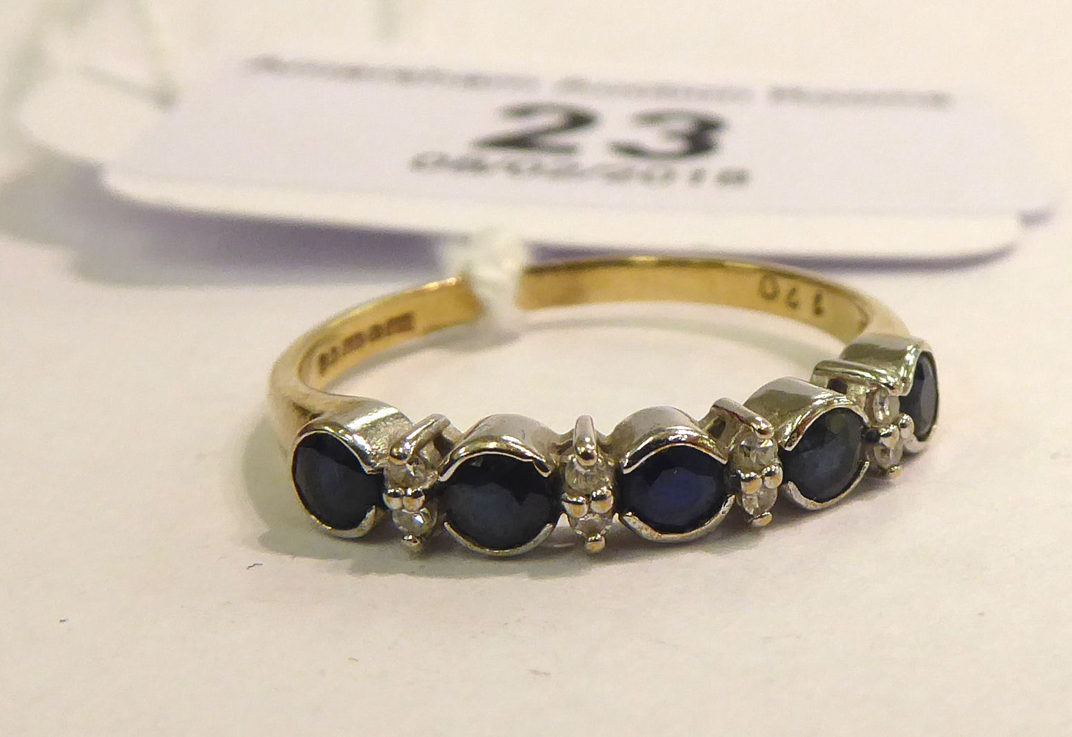 Lot 23 - A 9ct gold five stone sapphire and diamond set half eternity ring 11