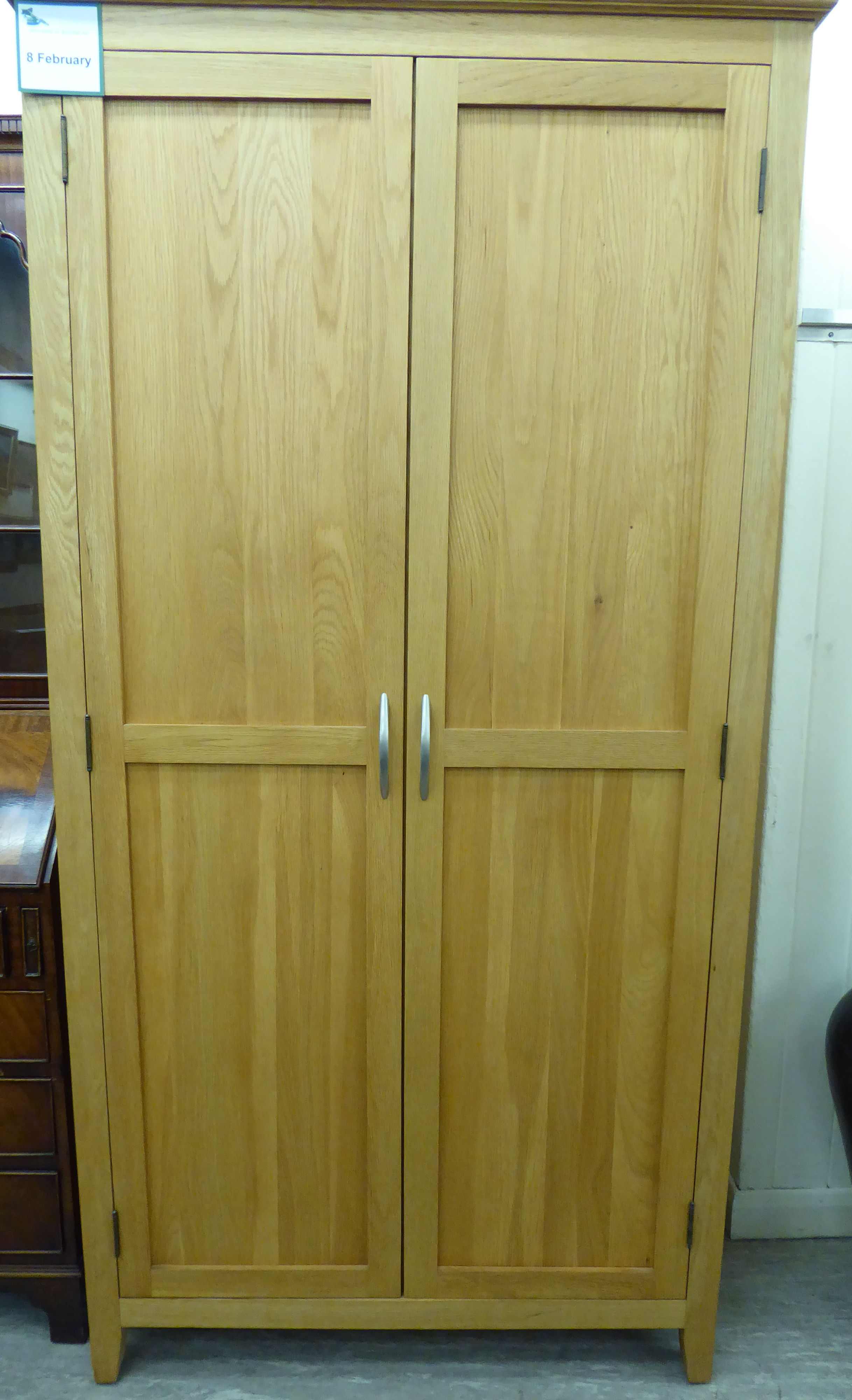 Lot 66 - A modern light oak finished wardrobe with a moulded cornice, over a pair of panelled doors,